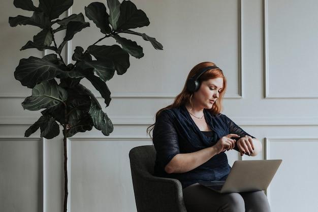 Kobieta ze słuchawkami i laptopem patrząca na zegarek