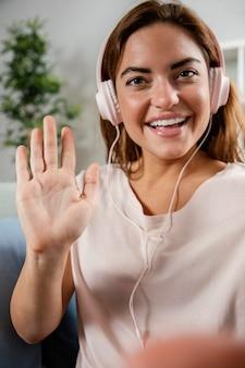 Kobieta ze słuchawkami macha