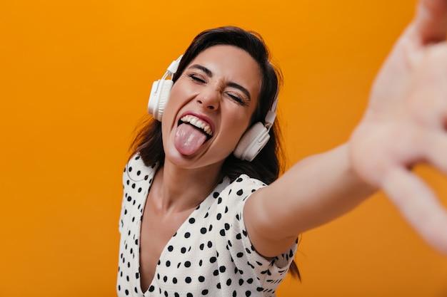 Kobieta ze słuchawkami pokazuje język i sprawia, że selfie na pomarańczowym tle. wesoła dziewczyna oddaje się białej bluzce w kropki.