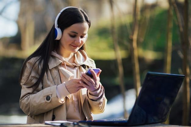 Kobieta ze słuchawkami pracuje na laptopie i używa smartfona