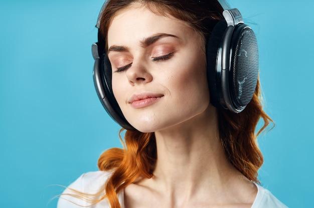 Kobieta ze słuchawkami słucha muzyki rozrywka technologia moda niebieskie tło