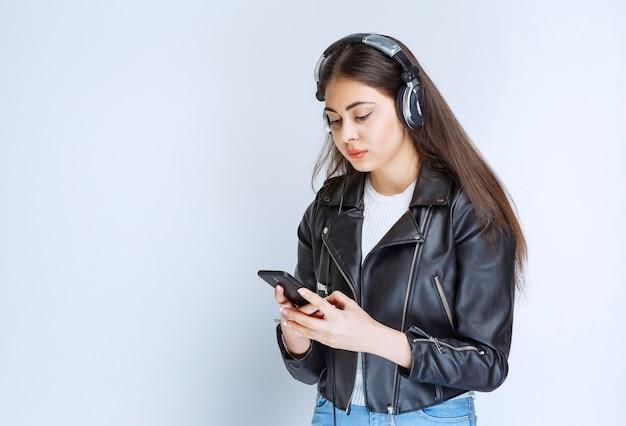Kobieta ze słuchawkami za pomocą swojego smartfona do ustawiania listy odtwarzania.