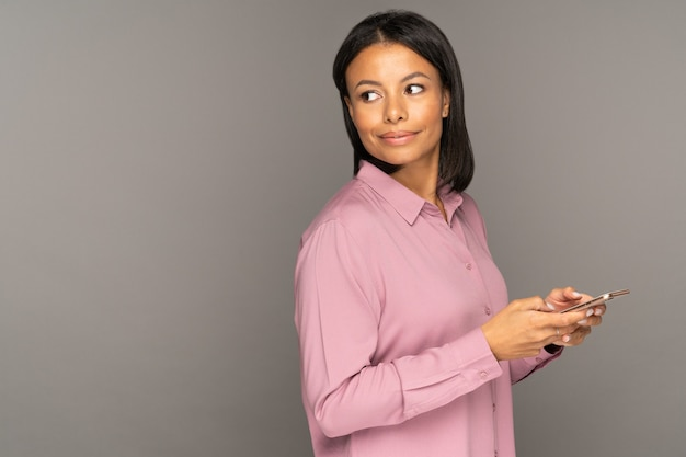 Kobieta ze smartfonem odwraca wzrok zaniepokojony od mediów społecznościowych przewijania z interesującymi reklamami lub produktem