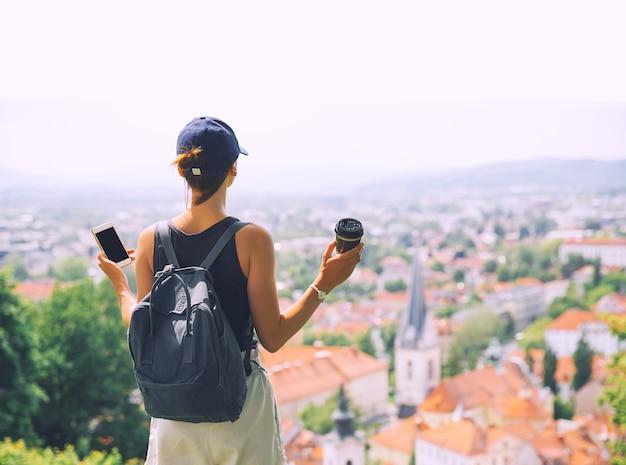 Kobieta ze smartfonem w dłoni na tle panoramicznego widoku z czerwonymi dachami miasta lublana