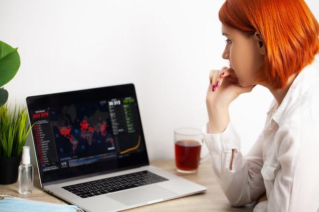 Kobieta ze smutkiem ogląda mapę rozprzestrzeniania się świata koronawirusów