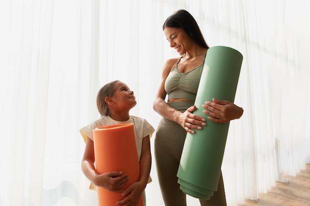 Kobieta ze średnim strzałem i dziecko z matą do jogi