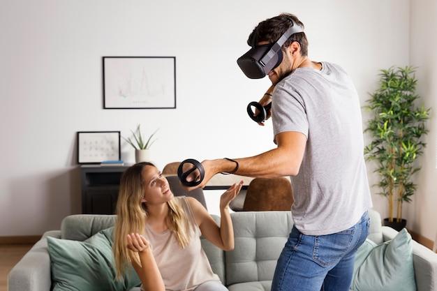 Kobieta ze średnim strzałem obserwująca mężczyznę grającego w grę