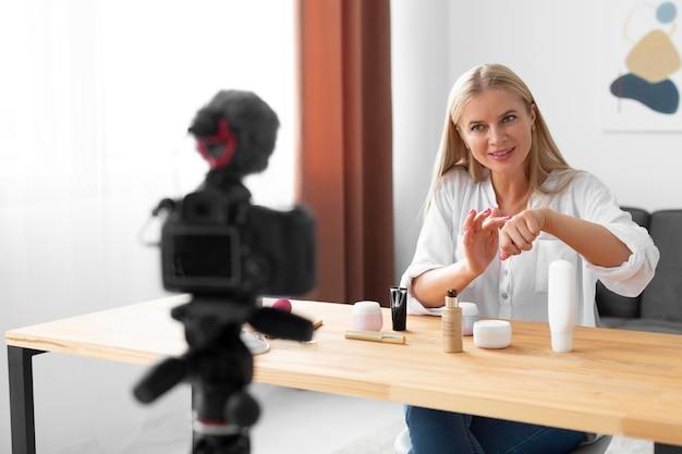 Kobieta ze średnim strzałem używająca produktu