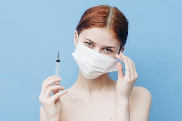 Kobieta ze strzykawką w dłoni i maską medyczną