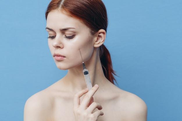 Kobieta ze strzykawkami w ręku dając zastrzyk w botoks odmładzający twarz