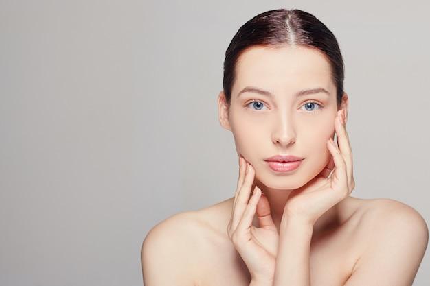 Kobieta ze świeżą, czystą skórą, która dotyka jej twarzy obiema rękami.