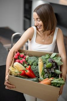 Kobieta ze świeżymi warzywami zapakowana w kartonowe pudełko w kuchni