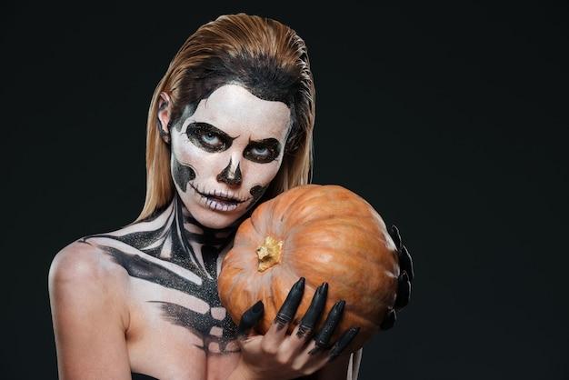 Kobieta ze szkieletowym makijażem halloween trzymająca dynię na czarnym tle