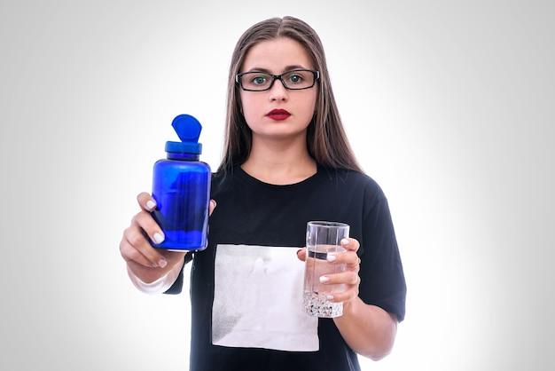 Kobieta ze szklanką wody i pigułki w butelce na białym tle