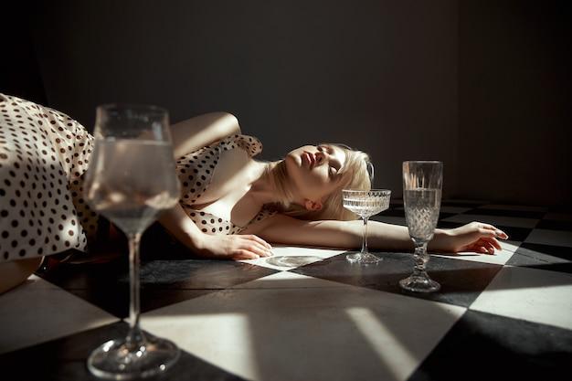 Kobieta ze szklanym alkoholem w dłoni leży na podłodze, stare wnętrze, romantyczny wygląd blondynki. cień okna na ciele kobiety
