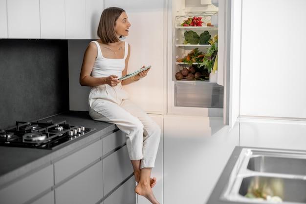 Kobieta ze zdrowymi warzywami w lodówce