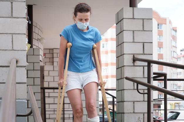 Kobieta ze złamaną nogą schodzi po rampie za pomocą kul ortopedycznych.