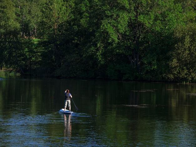 Kobieta żegluje po pięknej spokojnej zielonej lagunie. wakacje letnie wakacje. sup deska do wiosłowania na stojąco