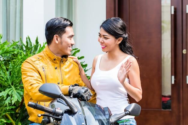 Kobieta żegna motocyklistę, który rano odjeżdża do pracy