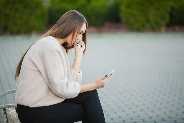 Kobieta zestresowana z pracy siedząc na zewnątrz, naciśnij od kolegów