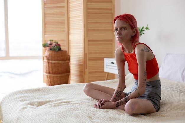 Kobieta źle się czuje. rudowłosa, niezdrowa kobieta z bulimią, siedząca na łóżku, czuje się źle i samotna