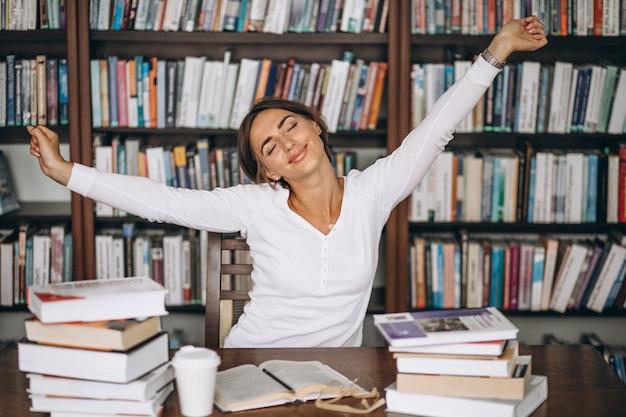 Kobieta zmęczona, rozciąganie w bibliotece