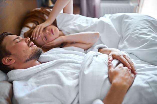 Kobieta zmęczona słuchaniem chrapiącego męża podczas snu