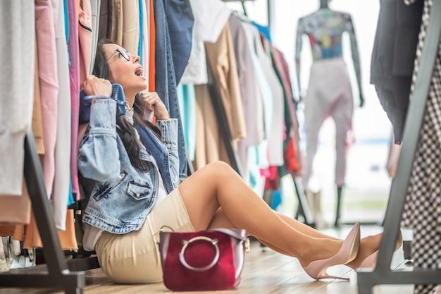 Kobieta zmęczona zakupami siedzi w rozpaczy na podłodze sklepu z modą wśród ubrań na wieszakach.