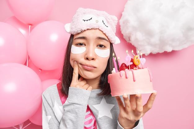 Kobieta zmusza uśmiech denerwuje się starzeniem trzyma pyszne truskawkowe ciasto świętuje urodziny sama ubrana w piżamę