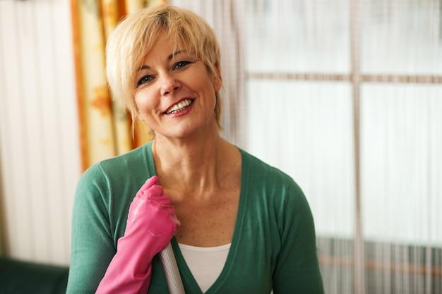 Kobieta zmywa podłogę w swoim domu