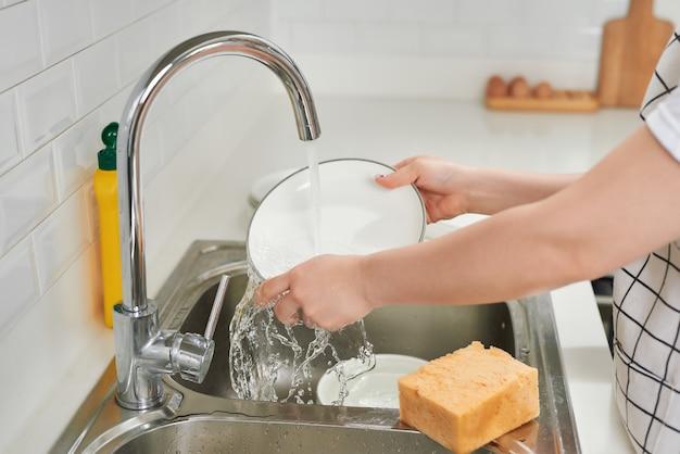 Kobieta zmywająca naczynia w kuchni