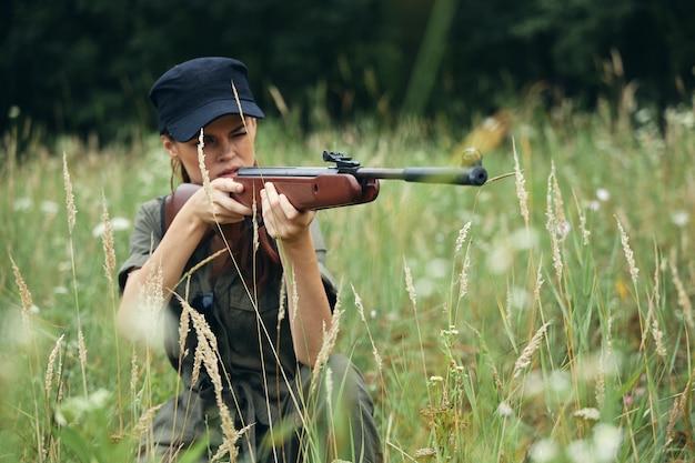Kobieta żołnierz z bronią w osłonie, czarną czapką myśliwską na zielonych drzewach