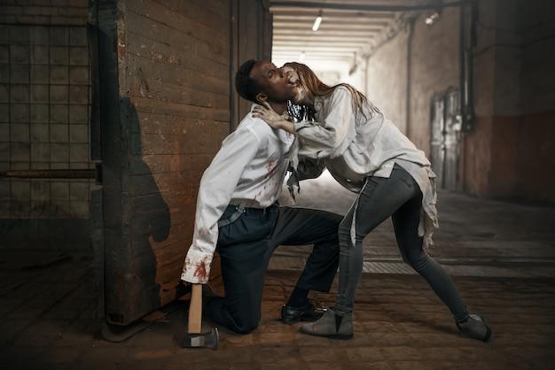 Kobieta zombie zaatakowała przerażonego mężczyznę toporem w opuszczonej fabryce. horror w mieście, przerażające crawlies, apokalipsa zagłady, krwawe, złe potwory