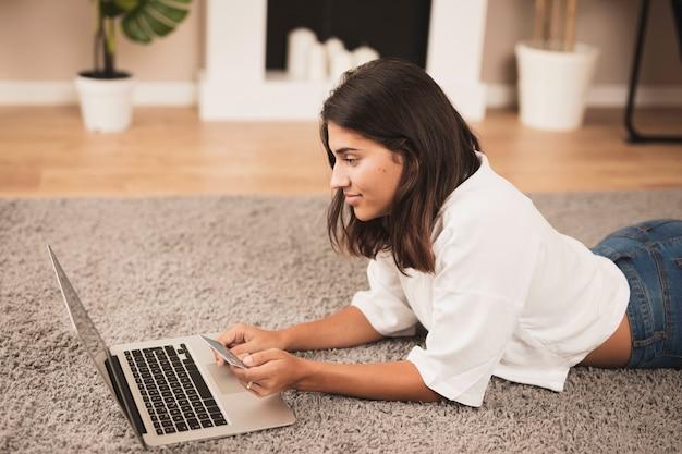 Kobieta zostaje na podłoga i pracuje na laptopie