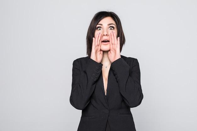 Kobieta zszokowana zabawnym, radosnym wyrazem twarzy na białym tle