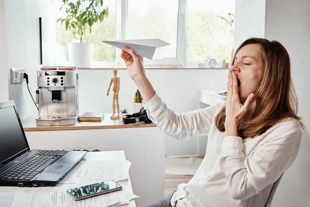 Kobieta zwleka w miejscu pracy freelancer na zdalnej pracy w domowym biurze niezmotywowana zmęczona kobieta bawi się papierowym zwykłym leniwym pracownikiem biurowym