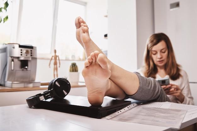 Kobieta zwleka z pracą zdalną. freelancer używa smartfona w domowym biurze