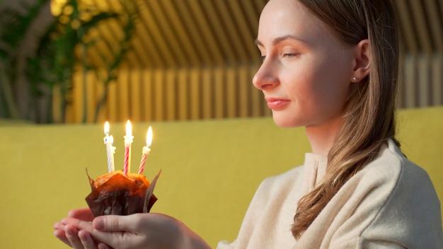 Kobieta życzy sobie, zdmuchuje świeczki na urodzinowym torcie i się śmieje