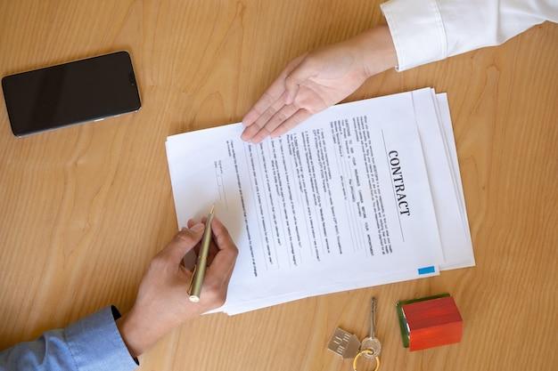Kobiety agent nieruchomości pokazuje, gdzie podpisać dokument na kupno umowy domu