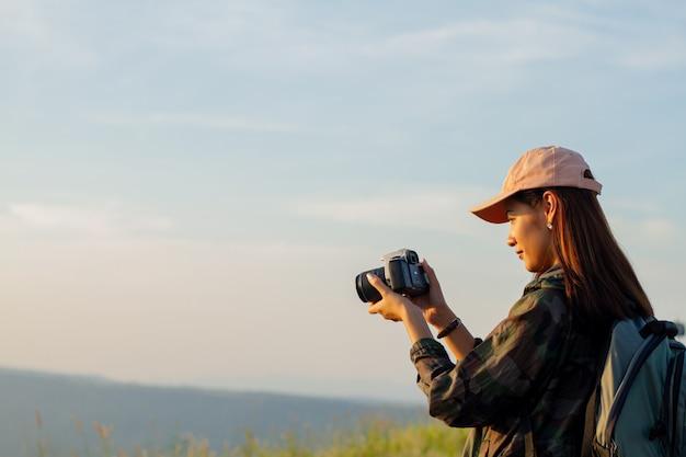 Kobiety azjatykcie z plecakiem bierze fotografię na widoku przy wschodu słońca nadmorski halnym szczytem