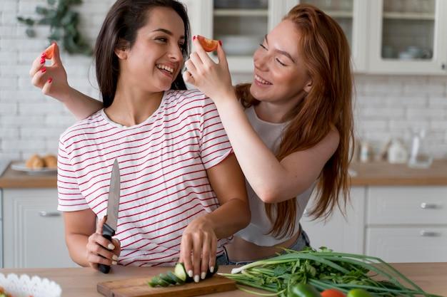 Kobiety bawiące się podczas przygotowywania posiłku