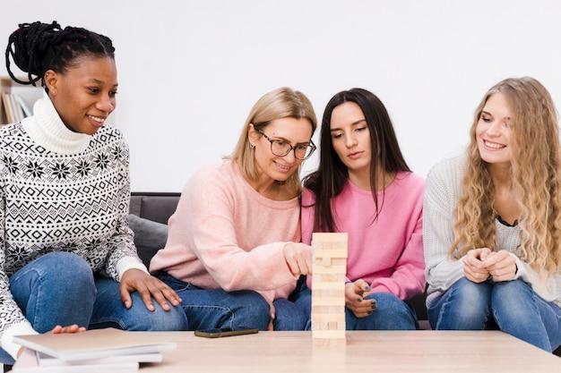 Kobiety bawiące się w drewnianą wieżę