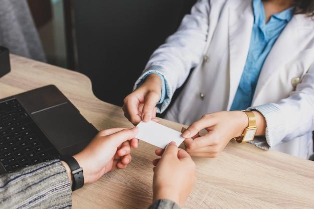 Kobiety biznesu, dając klientowi białą wizytówkę lub wizytówkę
