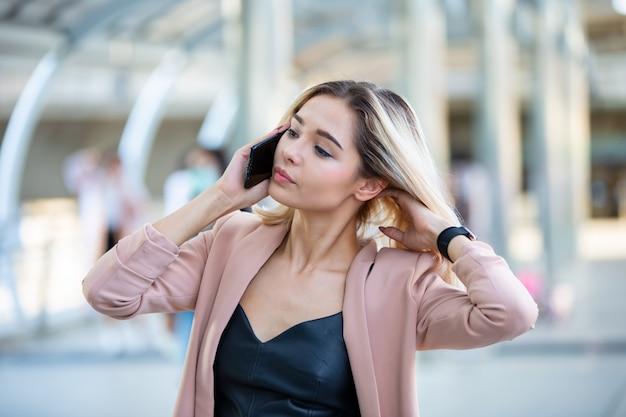 Kobiety biznesu dzwoni telefon komórkowy na zewnątrz