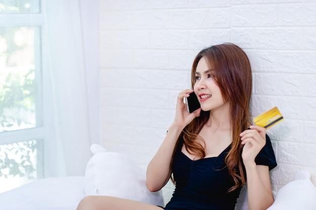 Kobiety biznesu rozmawiają przez telefon i posiadają kartę kredytową
