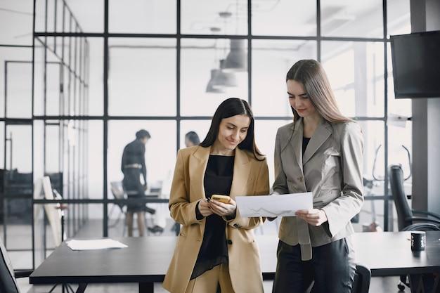 Kobiety biznesu rozmawiają przy biurku podczas przerwy na kawę w korytarzu dużej korporacji
