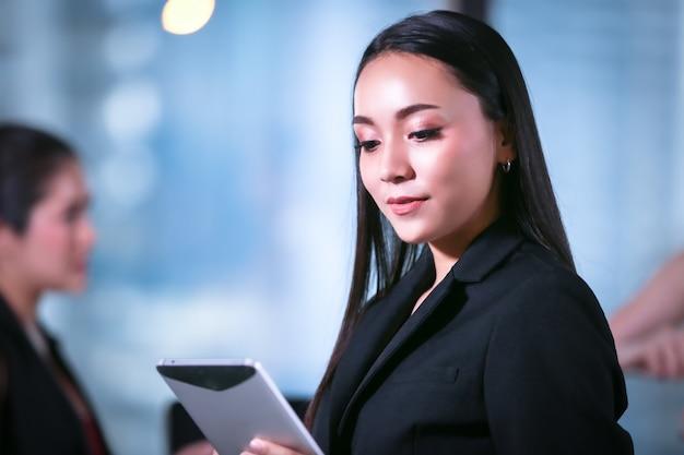Kobiety biznesu, trzymając tablet stojący w biurze
