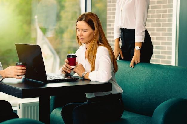 Kobiety biznesu w eleganckich, wizytowych strojach dyskutują o sprawach, używając laptopa, pijąc kawę i uśmiechając się podczas współpracy w kawiarni. spotkanie biznesowe w nowoczesnym wnętrzu w stylu loftu z cegły
