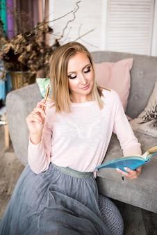 Kobiety blondynki włosiana szara kanapa, siedzący z notatnikiem i piórem, planuje w nowożytnym lekkim domu.