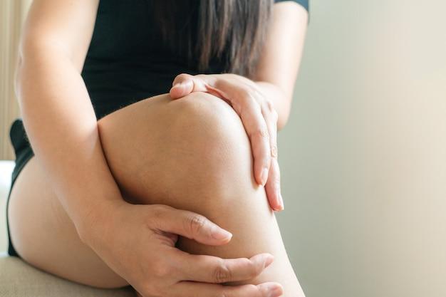 Kobiety boli kolano, kobiety dotykają kolana bólu w domu
